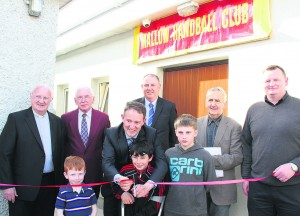 Minister of State, Sean Sherlock, with assistance from Eric Delany, Daniel O'Driscoll and Darragh Bowen, cuts the ribbon to officially open the extension to Mallow Handball Club, Also pictured, Canon Gerard Casey, Willie Mills who built the extension, John Harkin, John Ryan, and Club Chairman Ken O'Neill.