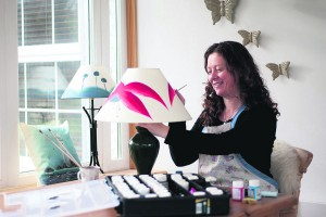 Olive Murphy of Olive Murphy Designs, working in her studio, handpainting a fuchsia lampshade.