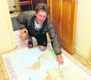 Marc Richard points to Ireland on his map which details his many cycle trips around the world.
