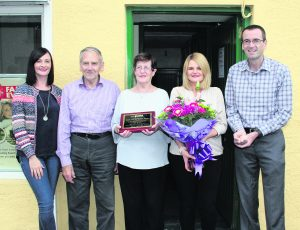 Margo Downes with her husband John and family. -- Margo Downes Retires from Pallaskenry Post Office -- Photo by Pat Madigan