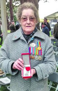 Barbara Allshire proudl wears her husband Jack's medals from WWII, while holding the Legion d'Honneur, at the presentation ceremony in Glasnevin Cemetery, Dublin, last Sunday.